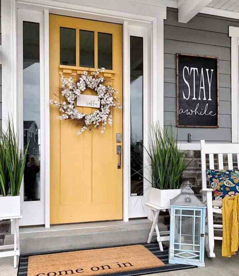 a cozy rustic porch with a mustard door, potted grasses, a candle lantern, a rocker and a sign is a lovely space