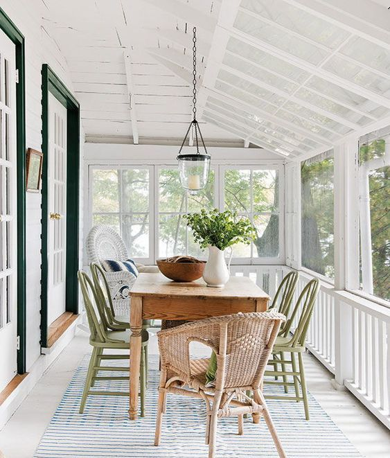 a cozy screened porch with a dining space - a wooden table, green and natural rattan chairs, greenery and a pendant lamp