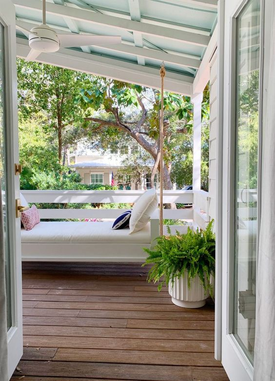 a cozy small porch with a white daybed hanging here and bright pillows plus a potted fern is a cool space to be