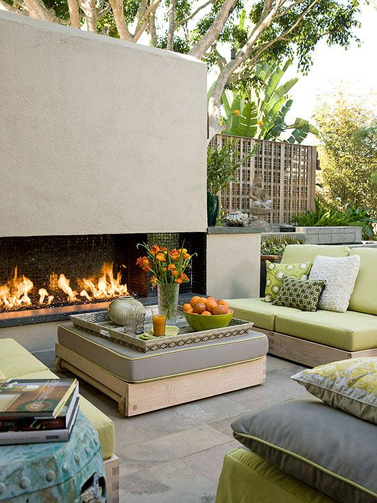 a cozy terrace with a fireplace, simple contemporary furniture with green upholstery, touches of orange for a stronger summer feel