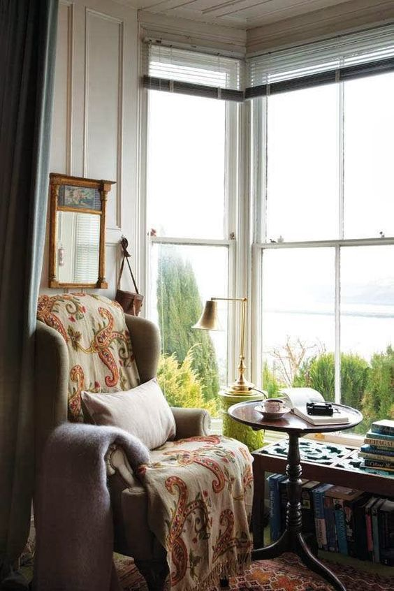a cozy vintage reading nook with a large corner window, a vintage chair and a low coffee table with books under it and printed textiles
