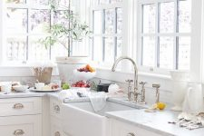 a cozy white farmhouse kitchen with shaker style cabinets, a corner French window that provides lovely views of the garden
