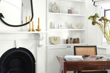 a creative and refined home office with a built-in storage unit, a metal fireplace, an asymmetrical mirror in a black mirror, black and white curtains, a rich stained desk and a rattan chair