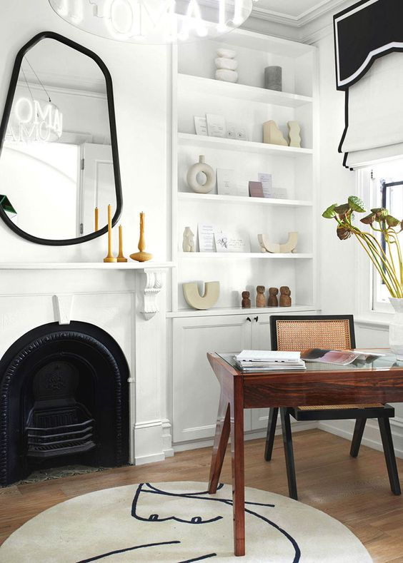 a creative and refined home office with a built in storage unit, a metal fireplace, an asymmetrical mirror in a black mirror, black and white curtains, a rich stained desk and a rattan chair