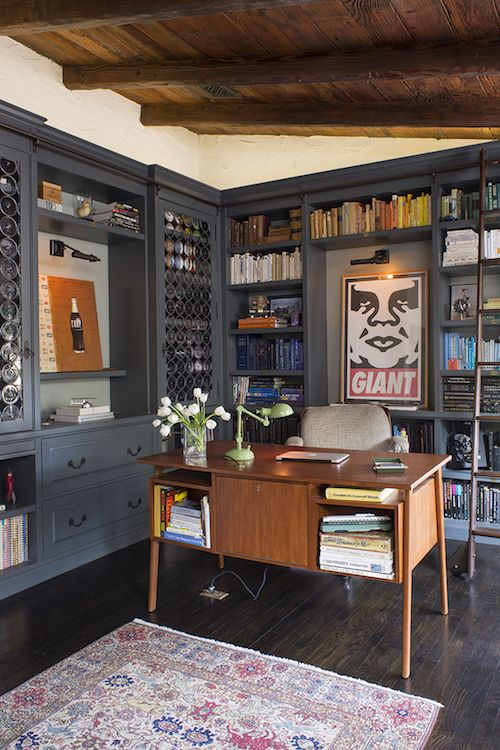 a creative home office with grey bookcases and storage units, a wooden ceiling with beams, a stained desk, a cozy chair and a printed rug