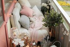 a cute balcony with a sofa with lots of pillows, potted plants and blooms, candle lanterns and string lights is a cool space