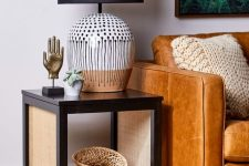 a dark side table with cane legs is a stylish and chic idea that brings texture and interest to the space