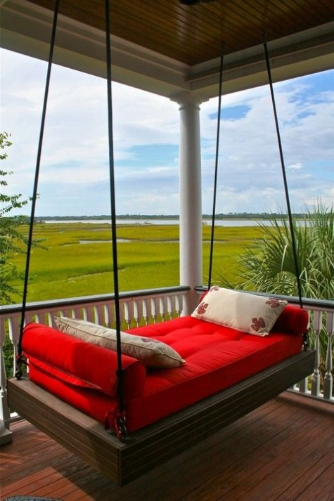 a dark stained daybed hung on the porch, with a mattress and bold pillows and a lovely view right form the porch is a dreamy space
