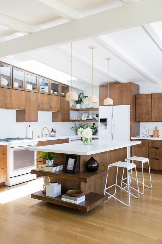 a dark stained mid-century modern kitchen with white countertops, white stools, pendant lamps, gold fixtures is a lovely space