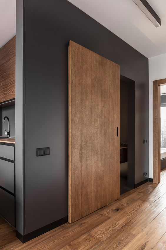 a dark-stained sleek wooden sliding door with a small handle is a cool solution for a laconic grey apartment