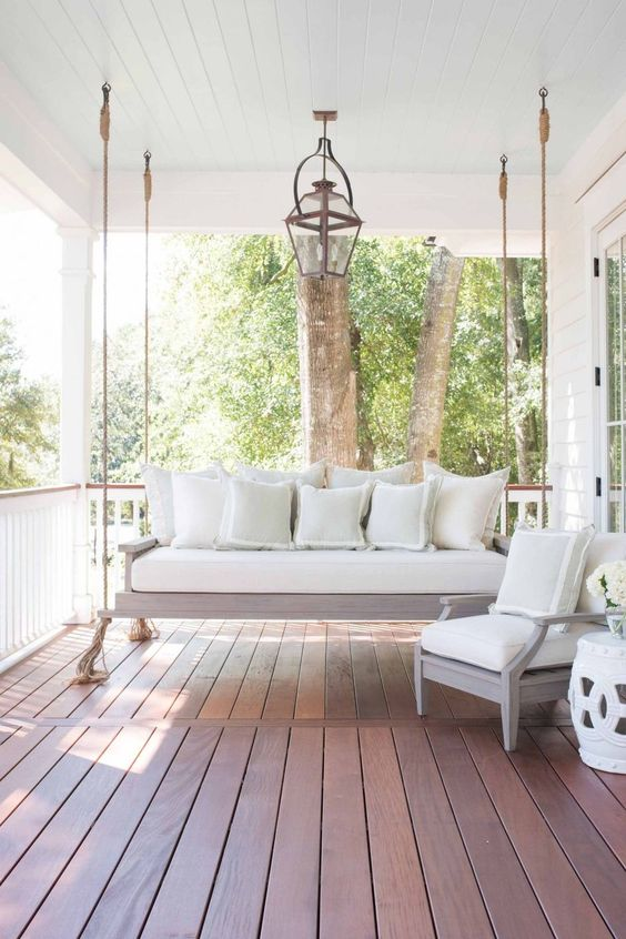 a delicate vintage farmhouse porch with a neutral hanging daybed with pillows, a chair with matching pillows and a side table with blooms