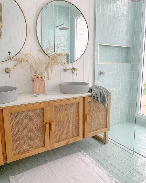a double vanity with cane doors, round concrete sinks, round mirrors composes a very chic bathing space