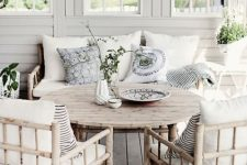 a dreamy Nordic veranda with bamboo furniture including a round table, neutral and printed bedding, potted greenery is wow