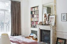 a dreamy Parisian bedroom with a non-working fireplace, a bed with pink bedding, a glass nightstand, a built-in bookcase and lovely art