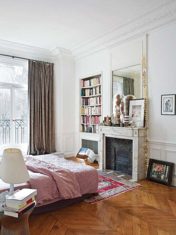a dreamy Parisian bedroom with a non working fireplace, a bed with pink bedding, a glass nightstand, a built in bookcase and lovely art