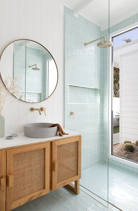 a dreamy mid-century modern bathroom with white and mint blue tiles, a rattan vanity, a round mirror and a round sink