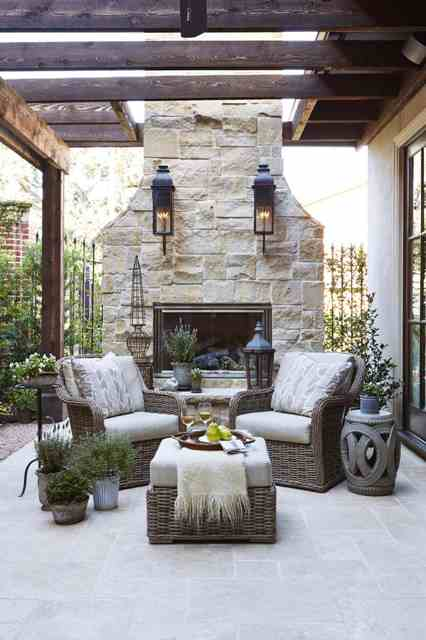 a dreamy rustic terrace with a stone fireplace, wicker furniture, potted plants, candle lanterns is a very inviting and beautiful space