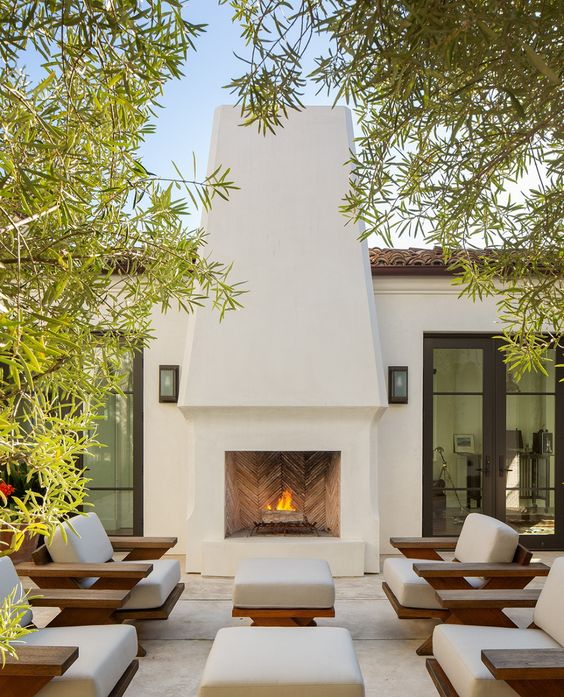 a fab modern outdoor space with a large white stucco fireplace, stained and white chairs and ottomans is a very chic and elegant terrace