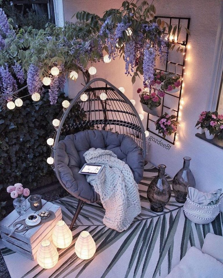 a fab outdoor space with lots of blooms, a rattan egg-shaped chair, a printed rug, some candle lanterns and vases for decor is very cozy
