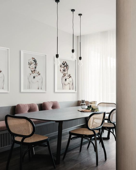 a fabulous dining room with a built in bench and pink pillows, a rounded table, black and neutral stained cane chairs and a small gallery wall