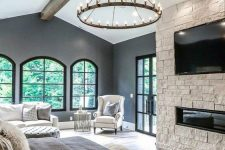 a fabulous farmhouse bedroom with arched windows and doors to the garden, a white sofa and an ottoman, a white chair, neutral bedding and a built-in fireplace