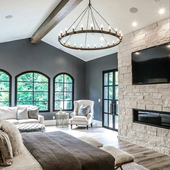 a fabulous farmhouse bedroom with arched windows and doors to the garden, a white sofa and an ottoman, a white chair, neutral bedding and a built in fireplace