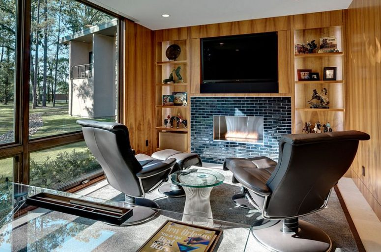 a fabulous home office with a glass desk, leather chairs and a glass side table, a fireplace clad with navy tiles, built-in shelves