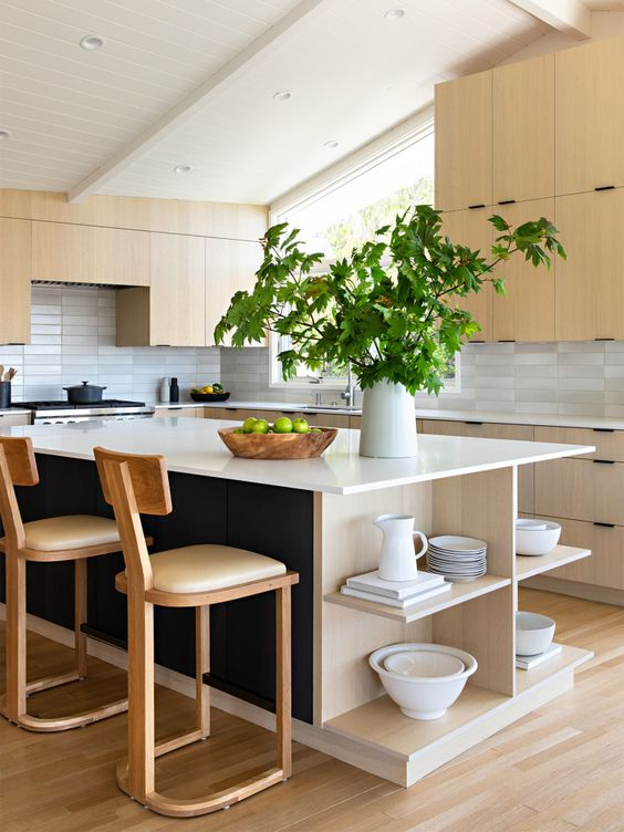 a fabulous mid-century modern kitchen with light-stained cabinets, a black and neutral kitchen island, neutral stools and skinny tiles