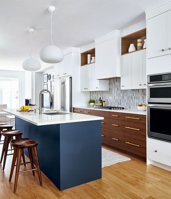 a fabulous mid-century modern kitchen with two tone cabinets, white countertops, a mosaic tile backsplash and a navy kitchen island