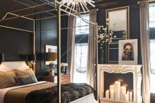 a fantastic glam bedroom with black walls, a gold canopy bed with pretty bedding, a sunburst chandelier, a fireplace wiht candles and layered rugs