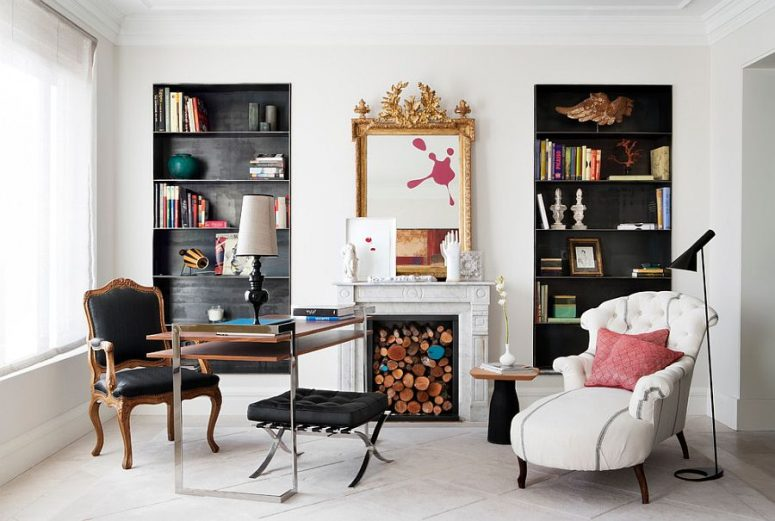 a fantastic home office with built-in shelves in black niches, a two tiered desk, a black chair and stool and a white lounger plus a fireplace with some wood