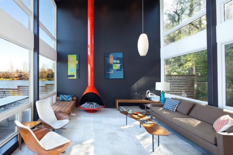 a fantastic mid-century modern living room with a taupe sofa, a brown leather couch, a fiery red hearth, colorful artworks and lovely chairs