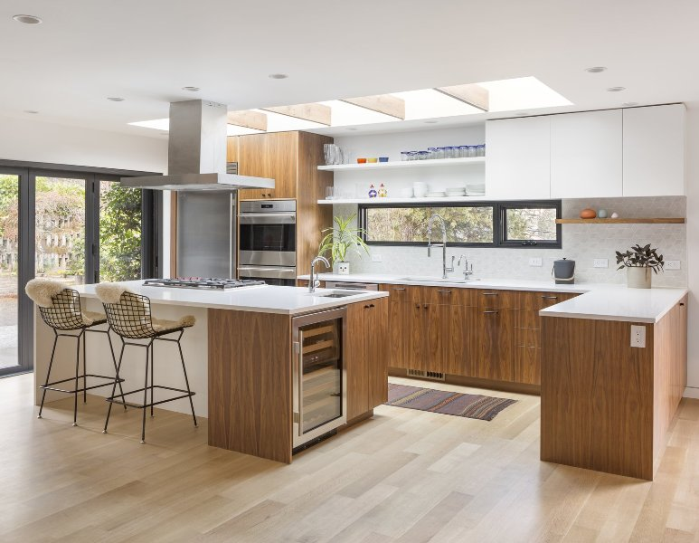 a fantastic mid-century modern stained kitchen with white countertops, a geo tile backsplash, a window and skylights