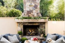 a fantastic rustic terrace with a stone fireplace, rough wood sofas and a wooden table, greenery and blooms and grass is wow
