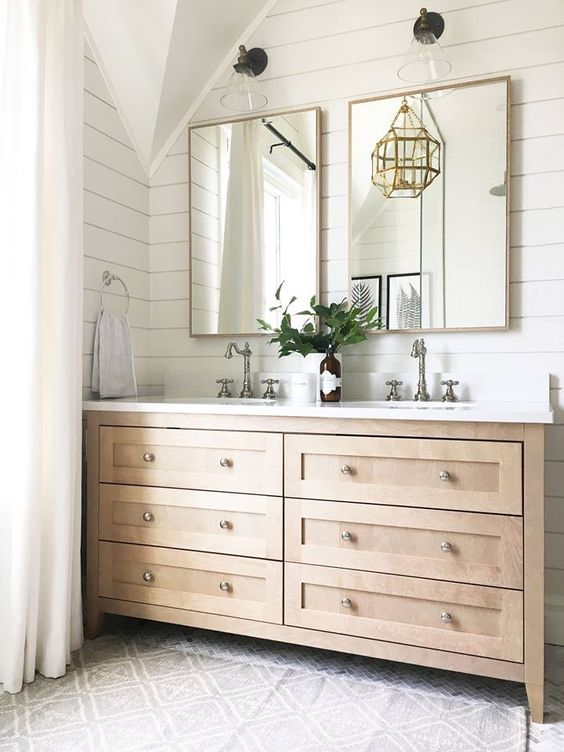 a farmhouse bathroom with a stained wooden vanity, mirrors in brass frames, a gold pendant lamp and delicate silver finish fixtures
