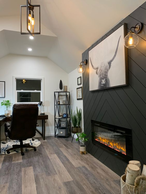 a farmhouse home office with a built-in fireplace clad with grey planked, a dark stained corner desk, a leather chair and potted plants