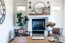 a farmhouse home office with white planked walls, a built-in fireplace, a trestle desk, leather chairs and a black one, some decor and plants