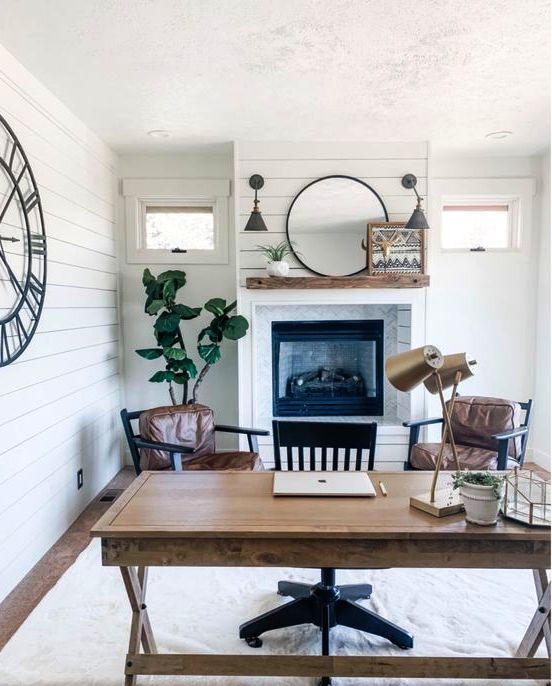 a farmhouse home office with white planked walls, a built in fireplace, a trestle desk, leather chairs and a black one, some decor and plants