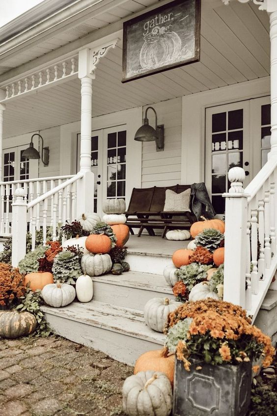 a farmhouse porch with a dark stained bench and pillows, lots of bright blooms and pumpkins on the steps is a cool idea