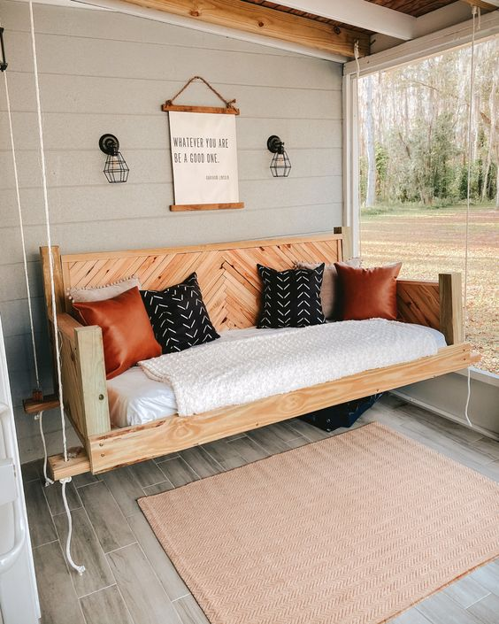 a farmhouse porch with a hanging bed of stained wood with printed pillows, sconces, an artwork and a rug is a very cozy space