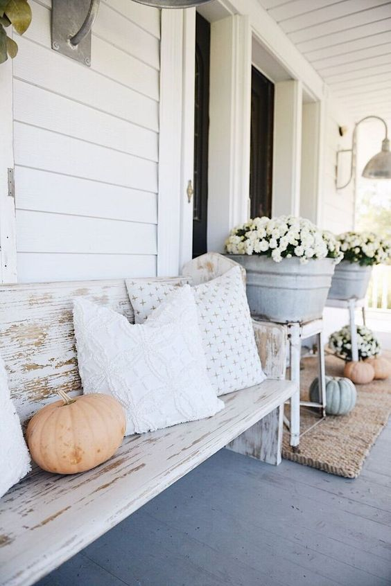 a farmhouse porch with a shabby whitewashed bench with pillows, potted blooms and some pumpkins is a cozy space