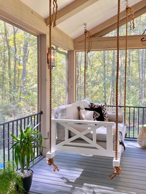 a farmhouse porch with a white hanging bed and printed pillows, potted plants and a candle lantern is a lovely idea to rock