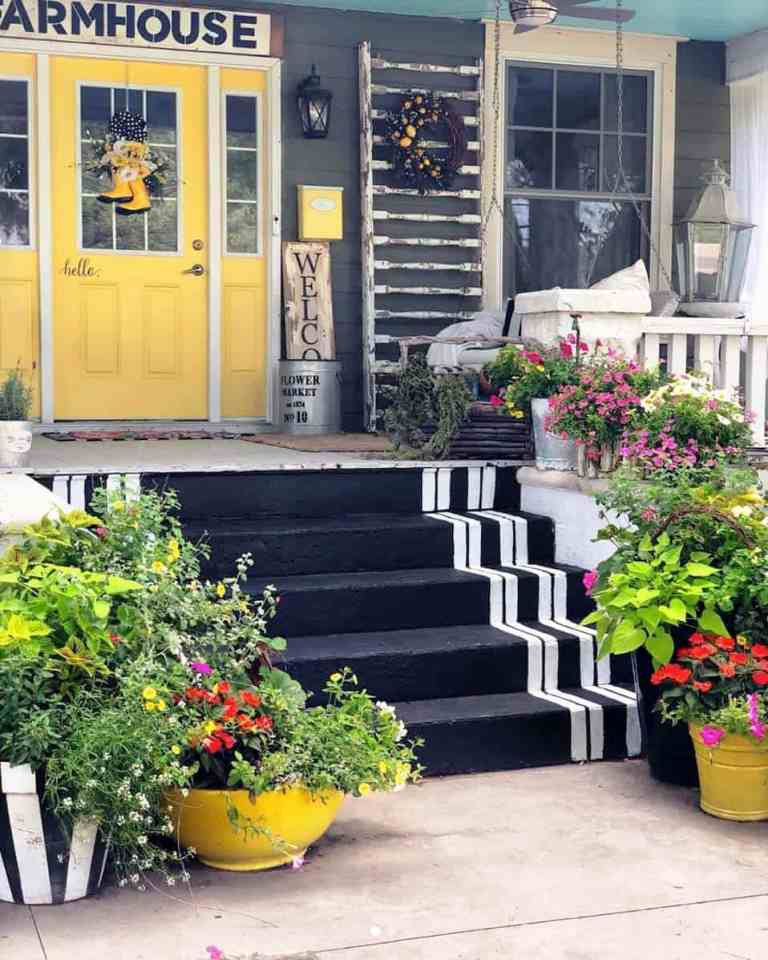 a farmhouse porch with a yellow door, a shabby ladder with a wreath for decor, a hanging bench and a bucket