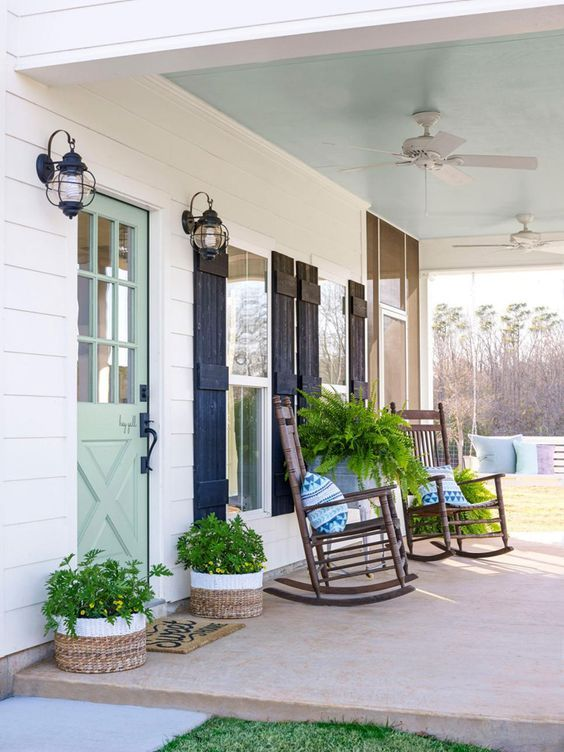 a farmhouse porch with navy shutters, stained rockers, potted greenery in buckets and baskets plus printed pillows