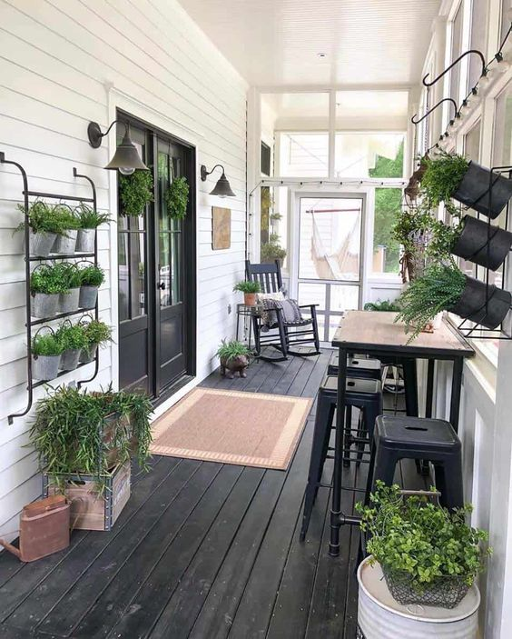 a farmhouse screened porch in black and white, with a rocker chair, a tall table and black stools, potted herbs in black planters