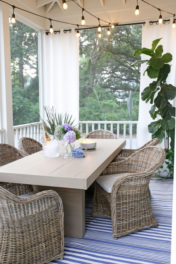 a farmhouse screened porch with a planked dining table, woven chairs, string lights, potted plants and views of the woodland
