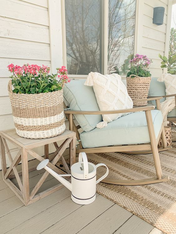 a farmhouse summer porch with stained furniture, blooms in baskets, a woven rug and printed pillows is a lovely space