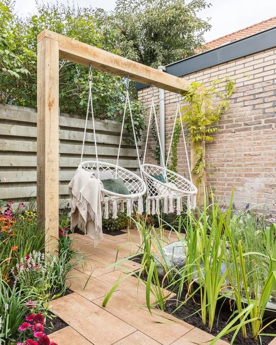 a fresh and welcoming outdoor space with growing greenery and flowers and with macrame hanging chairs that act as swings