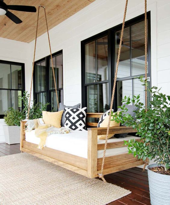a front porch with an outdoor hanging bed with bright pillows and a blanket, with potted plants and a jute rug is a stylish space