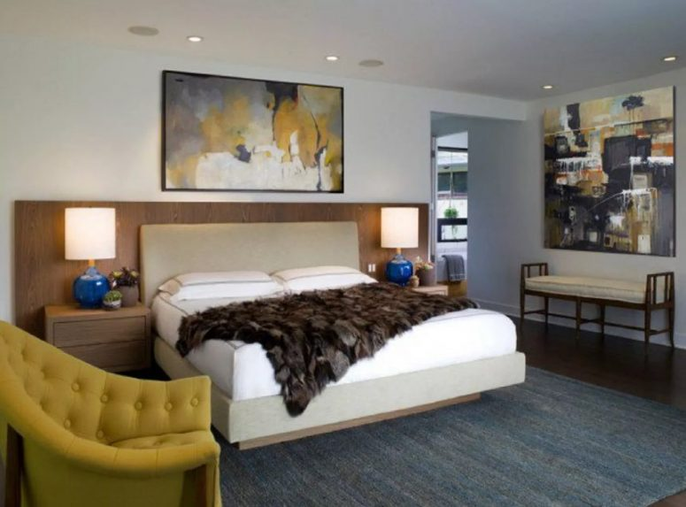 a glam mid-century modern bedroom with a floating bed, matching nightstands, a mustard chair and a bold artwork
